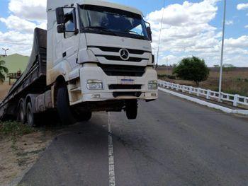 Caminhão perdeu tração, saiu da pista e ficou pendurado em ponte