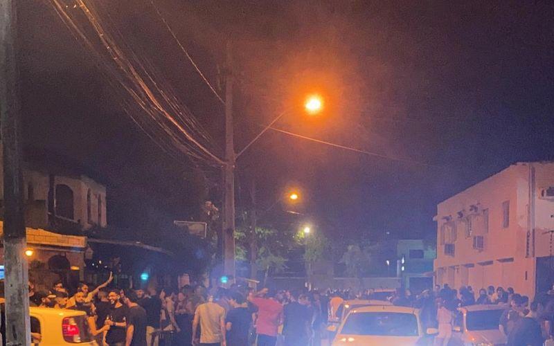 Pessoas aglomeradas na porta do bar