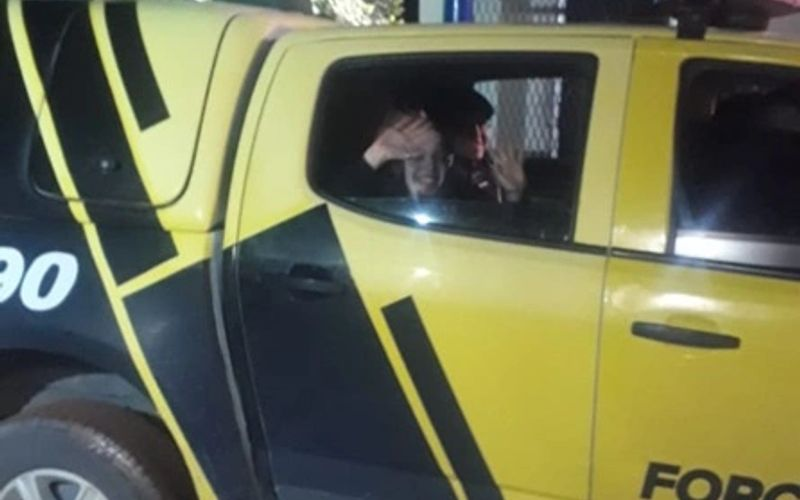 Mariana acena para populares de dentro da viatura da polícia, após ser resgatada.