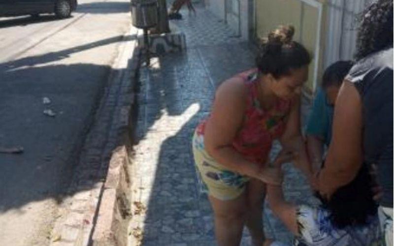Dona de cachorro atacado e morto por pitbull é amparada por vizinhos.